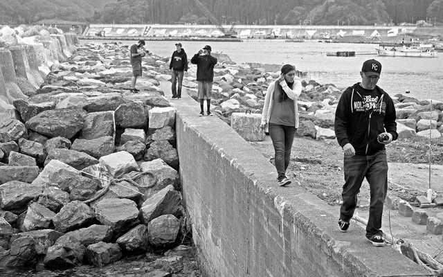 12-1100 Checking out the rebuilt harbor wall in the port of Taro Iwate the old tsumani wall is in the background