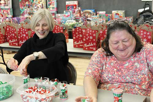 Mary Flynn, left, daughter of Christmas Stocking founder Katheryn Etter, packs candy for senior cheer boxes with Monda Hess