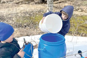 Thatcher and Atleigh making syrup